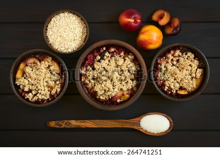 Overhead shot of three rustic bowls filled with baked plum and nectarine crumble or crisp, photographed on dark wood with natural light - stock photo