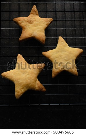 Overhead shot of three star shaped, home baked Christmas biscuits (cookies) on a black wire cooling rack.