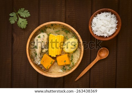 Overhead shot of traditional Chilean Cazuela de Pollo (or Cazuela de Ave) soup made of chicken, sweet corn, pumpkin, potato, seasoned with fresh coriander photographed on dark wood with natural light - stock photo