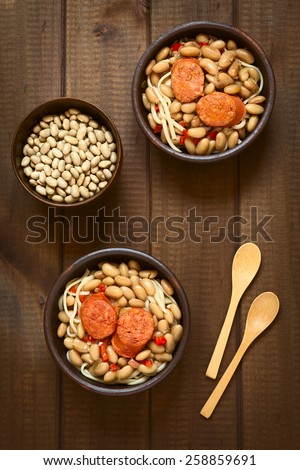 Overhead shot of traditional Chilean dish Porotos con Riendas (English: beans with reins), made of cooked beans, linguine (flat spaghetti), served with fried sausage, photographed with natural light - stock photo