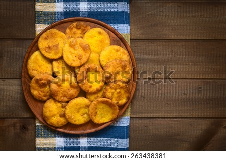 Overhead shot of traditional Chilean Sopaipilla fried pastry made with mashed pumpkin in the dough, served on wooden plate, photographed on wood with natural light - stock photo