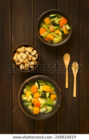 Overhead shot of two rustic bowls of vegetable soup made of zucchini, green bean, carrot, broccoli, potato and pumpkin with a small bowl of croutons, photographed on dark wood with natural light - stock photo