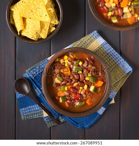 Overhead shot of vegetarian chili dish made with kidney bean, carrot, zucchini, bell pepper, sweet corn, tomato, onion, garlic, tortilla chips on the side, photographed on dark wood with natural light - stock photo
