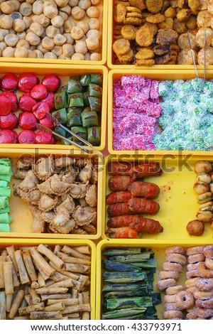 """Overhead shot over variety of delicious and colorful Malaysian home cooked local cakes or """"kueh"""" sold at street market stall in Kota Kinabalu Sabah from top angle view with seller arranging the cake. - stock photo"""