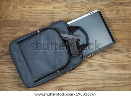 Overhead tilted view of laptop computer, personal weapon and carry case, on rustic wooden boards - stock photo