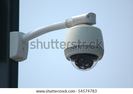 Overhead video security camera mounted on a pole, against a blue sky - stock photo