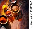 Overhead view depicting cooking with spices in a rustic kitchen with bowls of colourful ground spice and scattered powder on an old scored wooden counter with copyspace - stock photo