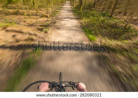 Overhead view of a Biker riding through a forest with motion blur - stock photo