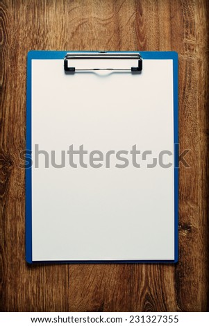 Overhead view of a blue clipboard with a blank sheet of white paper with copyspace for your text on a wooden table - stock photo
