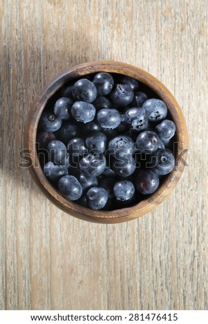 Overhead view of a bowl of blueberries sitting on a rustic wooden table. - stock photo