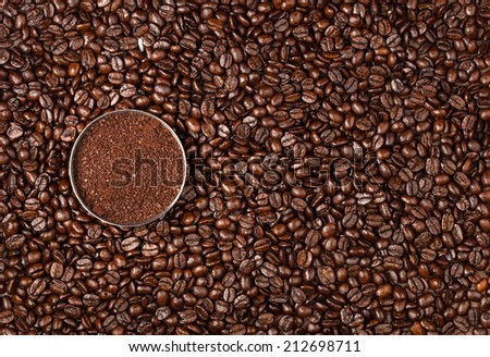 Overhead view of a bowl of ground coffee on a roasted whole, unground coffee bean background - stock photo
