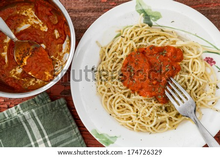 Overhead view of a bowl of tomato based Bolognese sauce and a serving of spaghetti pasta with sauce on a plate alongside - stock photo