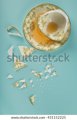 Overhead view of a Broken Elegant Vintage China Teacup with saucer dish, spilled tea and fractured shards of sharp glass fragments scattered on teal colored kitchen table background. Vertical