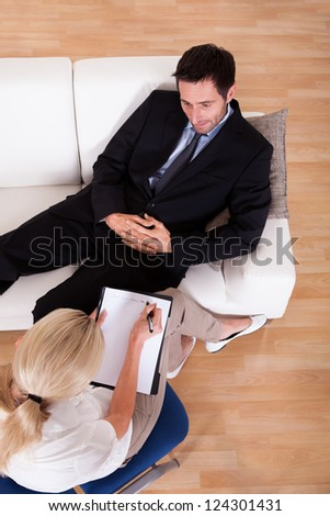 Overhead view of a business man reclining comfortably on a couch talking to his psychiatrist explaining something - stock photo