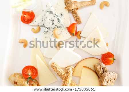 Overhead view of a cheese platter with cashew nuts and wedges of assorted hard cheeses, blue cheese and semi-soft cream cheese with sesame bread sticks and cherry tomatoes served as an appetizer - stock photo