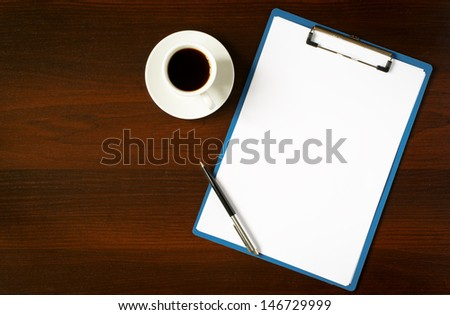 Overhead view of a clipboard with a blank sheet of white paper and a pen alongside a cup of espresso coffee on a black background with copyspace - stock photo