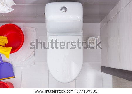 Overhead view of a closed toilet in a white and grey tiled bathroom with a colorful assortment of a plastic bucket, tub, pan and gloves for household cleaning - stock photo