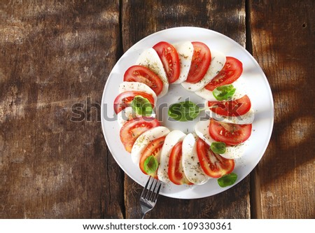 Overhead view of a decorative sliced tomato and cheese salad arranged alternately around a plate on an old textured wooden table - stock photo