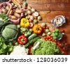 Overhead view of a delicious assortment of farm fresh vegetables, herbs and mushrooms spread out on a rustic wooden table - stock photo