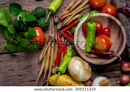 Overhead view of a delicious assortment of farm fresh vegetables, herbs and mushrooms spread out on a rustic wooden table