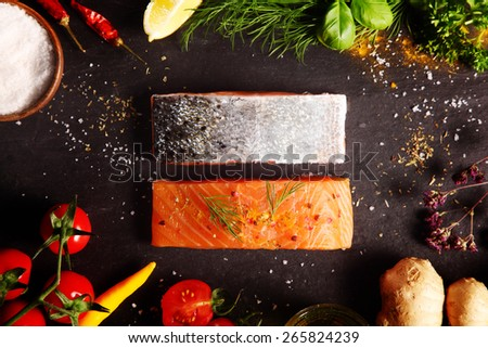 Overhead view of a frame of fresh ingredient including herbs, spices, root ginger, tomato, and chili pepper with raw salmon steaks for a gourmet recipe for a seafood dinner - stock photo