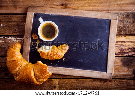 Overhead view of a fresh cup of coffee and a flaky croissant broken in two on an old school slate over a rustic wooden background, copyspace on the slate - stock photo