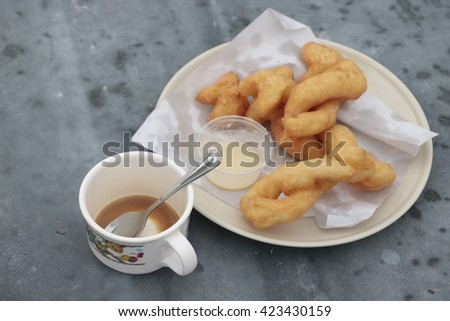 Overhead view of a fresh cup of coffee and a flaky croissant broken in two on an old school slate over a rustic wooden background,  - stock photo