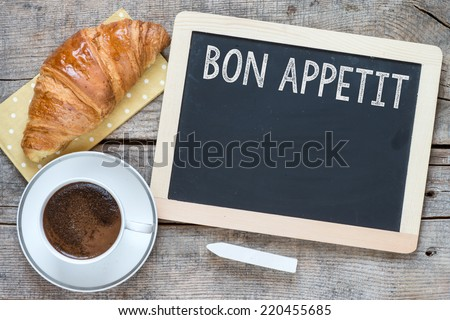 Overhead view of a fresh cup of coffee and a flaky croissant on an old school slate over a rustic wooden background.With text bon appetit on blackboard - stock photo