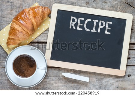 Overhead view of a fresh cup of coffee and a flaky croissant on an old school slate over a rustic wooden background.With text Recipe on blackboard - stock photo