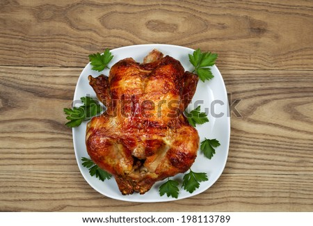 Overhead view of a freshly oven roasted whole chicken in white serving surrounded by large leaf parsley plate placed on rustic wood