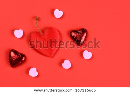 Overhead view of a group of Valentines Day candy on a red surface with copy space.