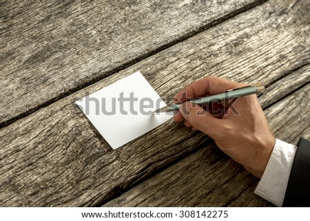 Overhead view of a hand in elegant suit writing on blank white card or paper with ballpoint pen on weathered old wooden desk, with copy space for you text. - stock photo