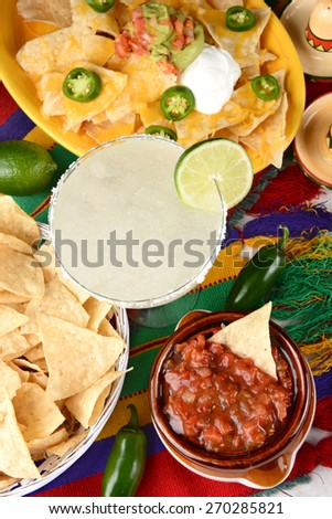 Overhead view of a margarita cocktail surrounded by nachos, chips, salsa on a bright Mexican, table cloth. Vertical format. Cinco de Mayo theme. - stock photo