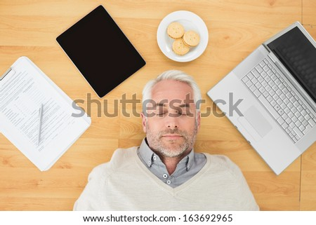 Overhead view of a mature man sleeping with electronics and biscuits on parquet floor at home