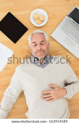 Overhead view of a mature man sleeping with electronics and biscuits on parquet floor at home - stock photo