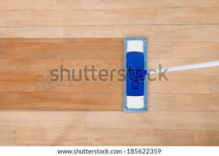 Overhead view of a modern sponge style mop being used for cleaning a wooden floor with copyspace - stock photo