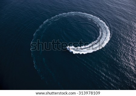 Overhead view of a motor boat making a turn in form of a swirl in the middle of the sea on a sunny day