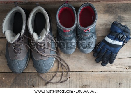 Overhead view of a pair of adult and kids snow boots standing ready on a rustic wooden floor alongside a pair if childs warm winter gloves to protect against the freezing cold weather, view from above - stock photo