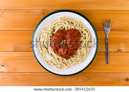 Overhead view of a plate of Italian spaghetti pasta served with a savory tomato sauce on a wooden garden table for a tasty lunch - stock photo