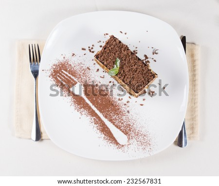 Overhead view of a portion of freshly baked cake topped with grated chocolate and decorated alongside with the outline of a fork in chocolate powder - stock photo