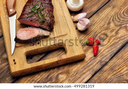 Overhead view of a portion of juicy grilled beef steak with on a textured wooden surface