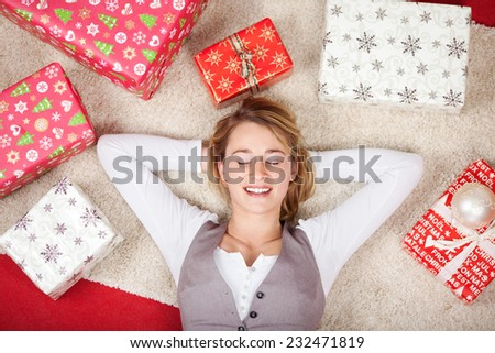 Overhead view of a pretty young woman surrounded with Christmas gifts lying on her back on the carpet with her eyes closed and a smile of contentment - stock photo