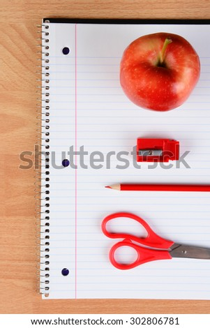 Overhead view of a red pair of scissors, red pencil, sharpener and apple on an open spiral notebook on a wood desk. Back to school concept. - stock photo
