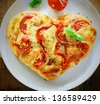 Overhead view of a romantic heart shaped Italian pizza topped with a vegetarian topping of golden melted cheese and tomato on a plain white plate. More pizza at my port. - stock photo