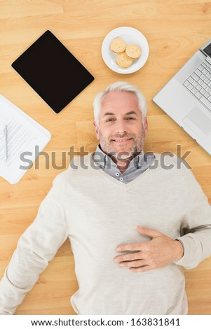 Overhead view of a smiling mature man lying with electronics and biscuits on parquet floor at home - stock photo