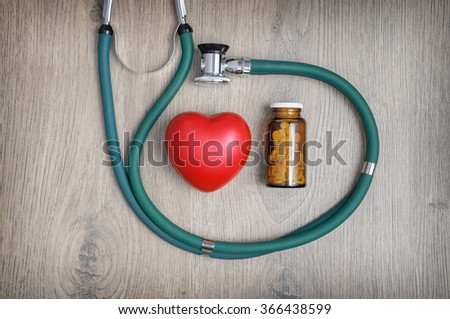Overhead view of a stethoscope, a glass of pills and a red heart shape  - stock photo