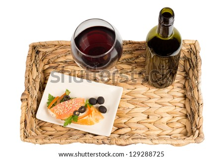 Overhead view of a tasty healthy meal of salmon steak served on a rustic woven tray with a glass and bottle of red wine - stock photo