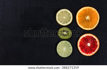 Overhead view of a variety of sliced citrus fruits, right side of layout, on black slate.  - stock photo