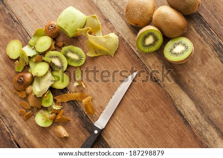 Overhead view of a wooden kitchen counter with a knife for preparing fresh tropical kiwifruit for a delicious dessert - stock photo
