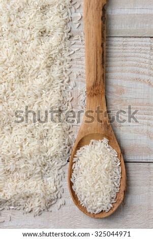 Overhead view of a wooden spoon full of rice next to a pile of more rice on a rustic wood table.